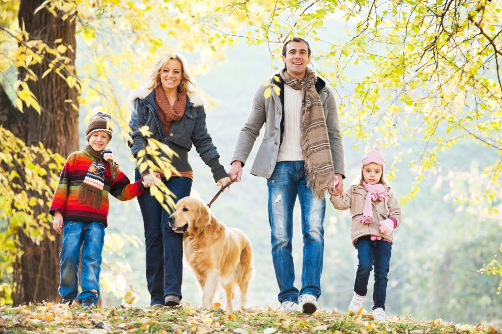 Family of four people walking a dog in park.